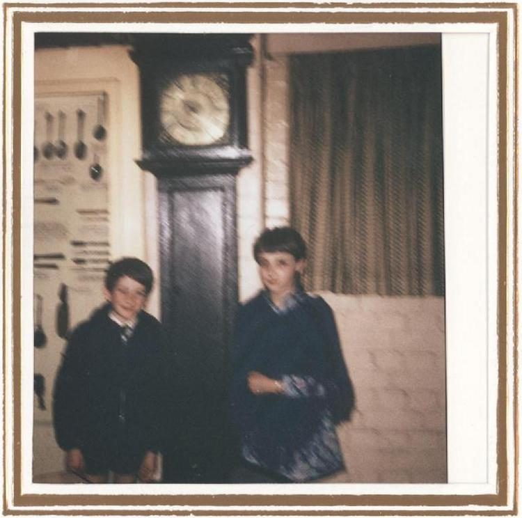 Martin Graeme Jeffries and Linda Merial Jeffries in front of the grandfather clock, Horniman Museum object no 15.10.51/1, presented by their grandfather A. E. Wiggins, whilst it was on display before 1978; the photograph was taken by their mother, Margaret Tebbs
