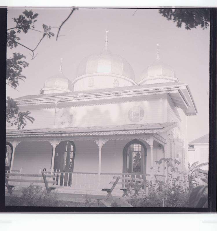 Black and white negative view of building with rounded turrets, front view, with shadows