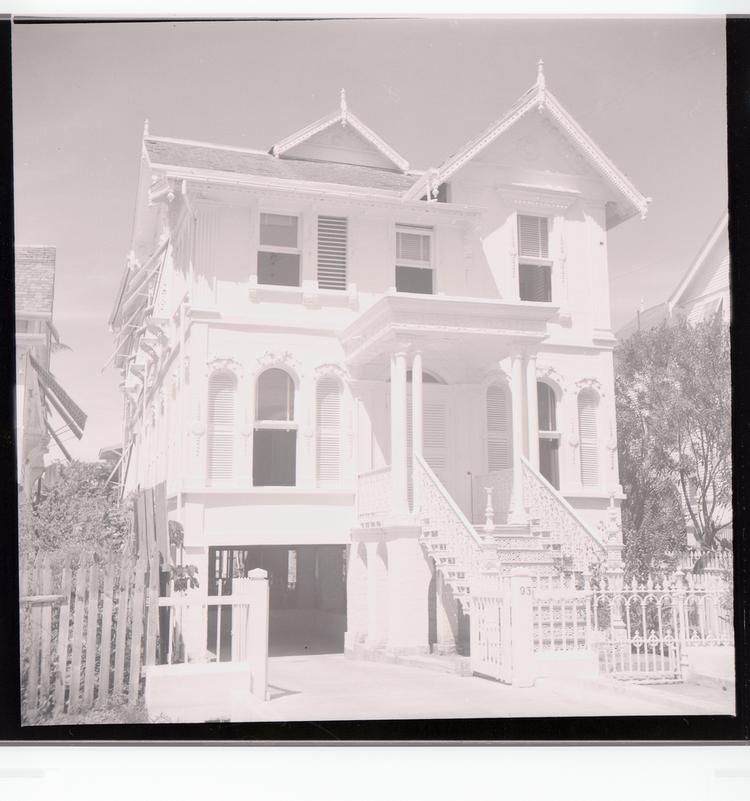 Black and white negative front view of multi-windowed house (number 93) with covered basement garage