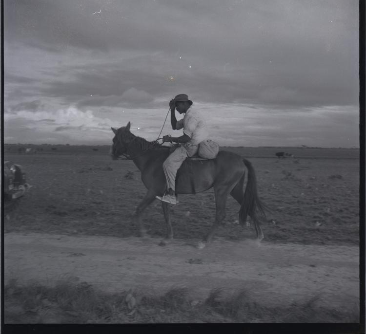 Black and white medium format negative of man riding a horse