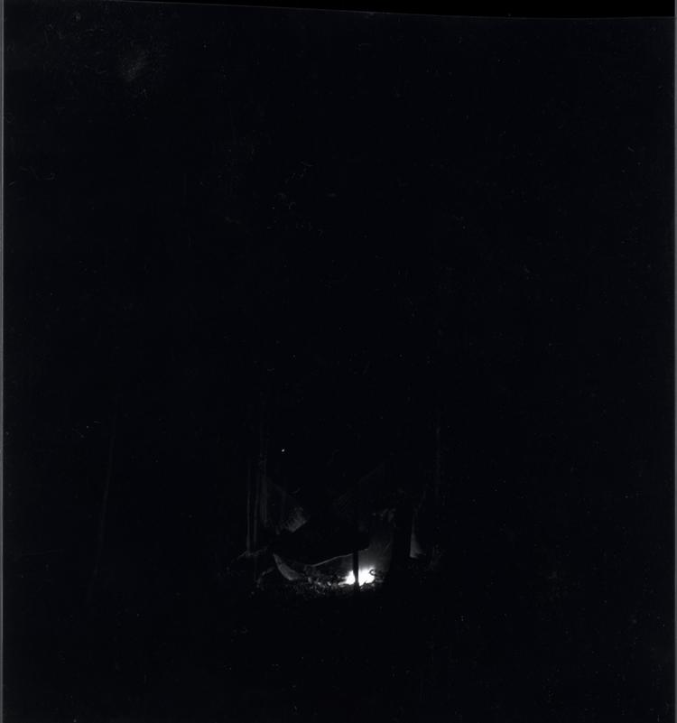 Black and white medium format negative of very dark with flames of a campfire