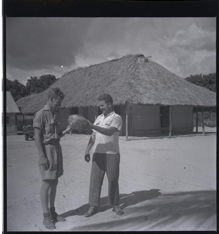 Black and white medium format negative of 2 men holding a rugby ball
