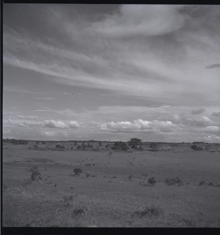 Black and white medium format negative of village of hut style houses in distance