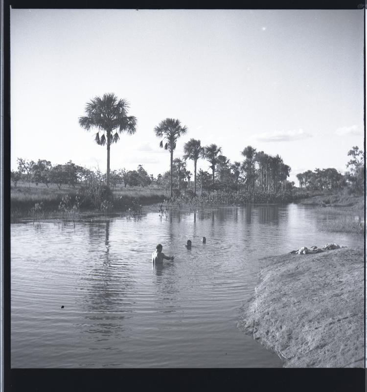 Black and white medium format negative of people bathing in a river