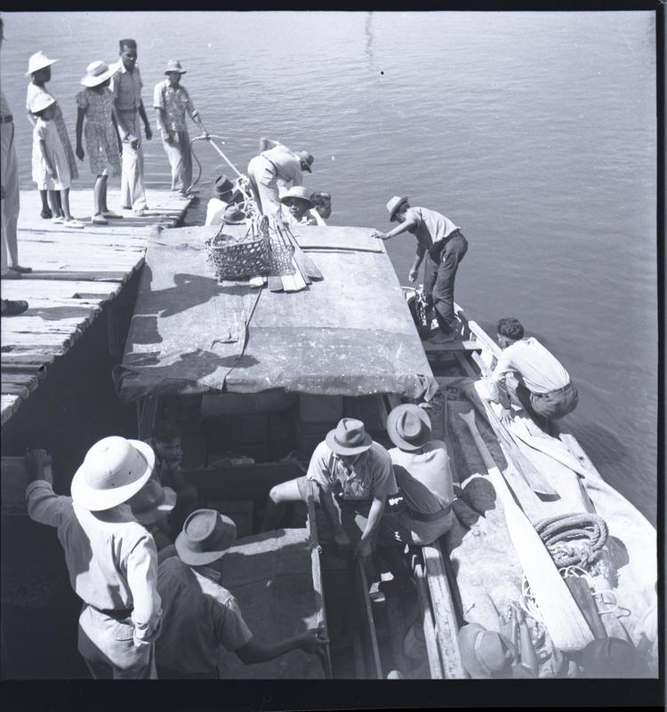 Black and white medium format negative of people on boats and landing stage