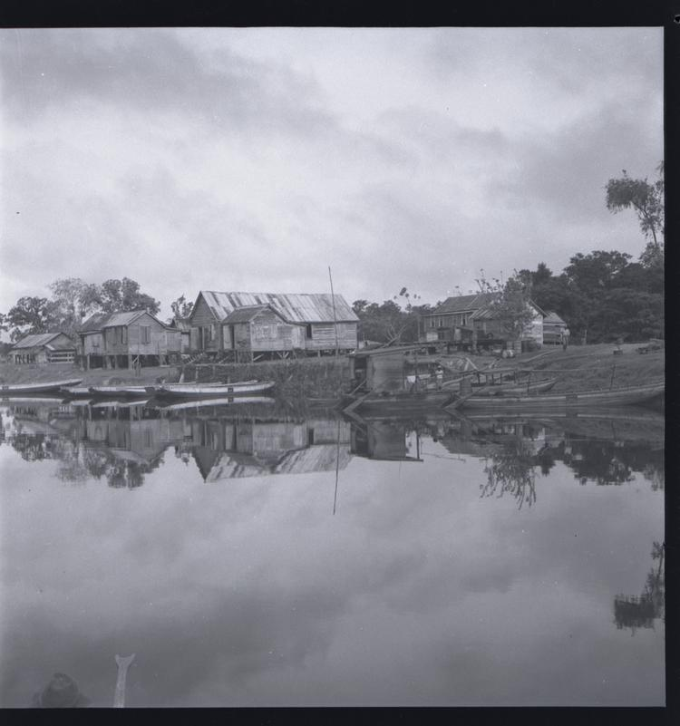 Black and white medium format negative of houses and boats seen from river with clear reflection