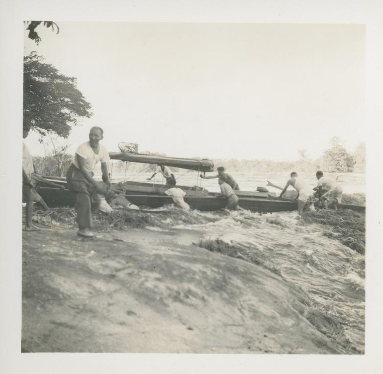 Black and white print of men in rapids moving boats