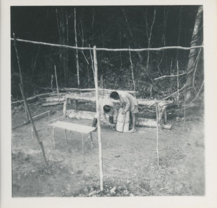 Black and white print of two people doing jobs at a camp in forest