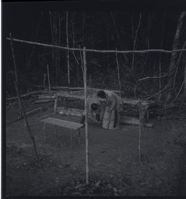 Black and white medium format negative of two people doing jobs at a camp in forest