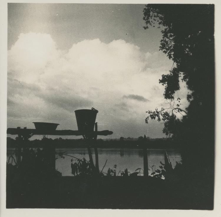 Black and white print of bucket and staging in silhouette with water and clouds behind