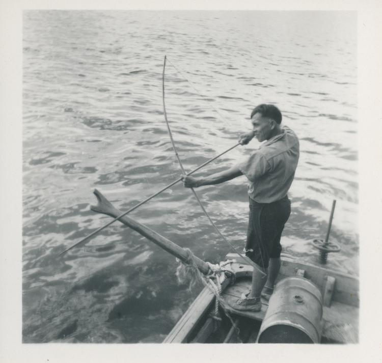 Black and white print of man standing in a boat aiming a bow and  arrow at the water