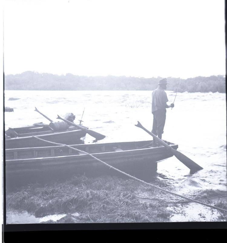 Black and white medium format negative of man standing on a boat fishing