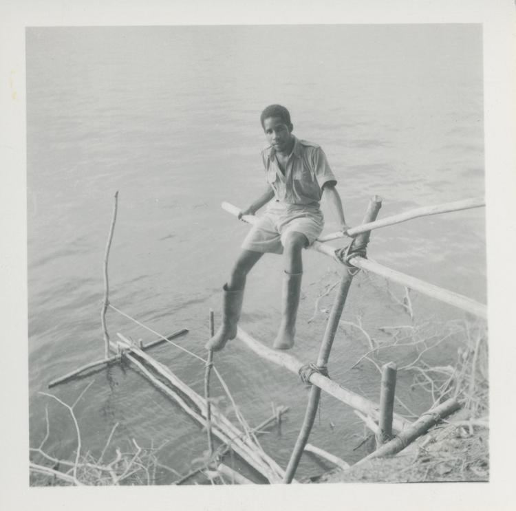 Black and white print of young man sitting on landing stage