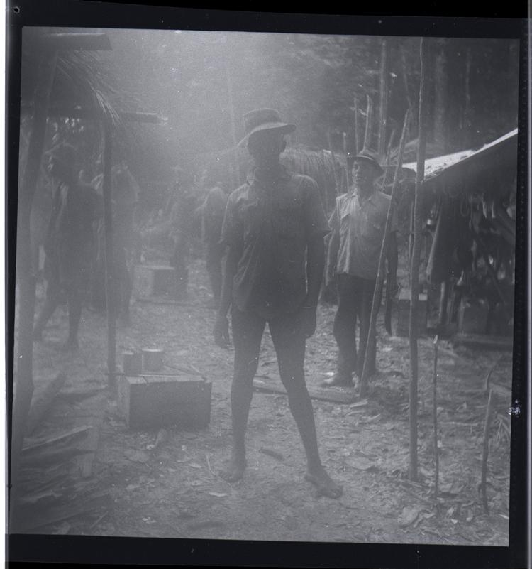 Black and white medium format negative of hazy image of men standing in camp area