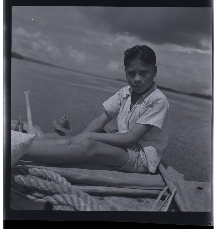 Black and white medium format negative of young boy on a boat
