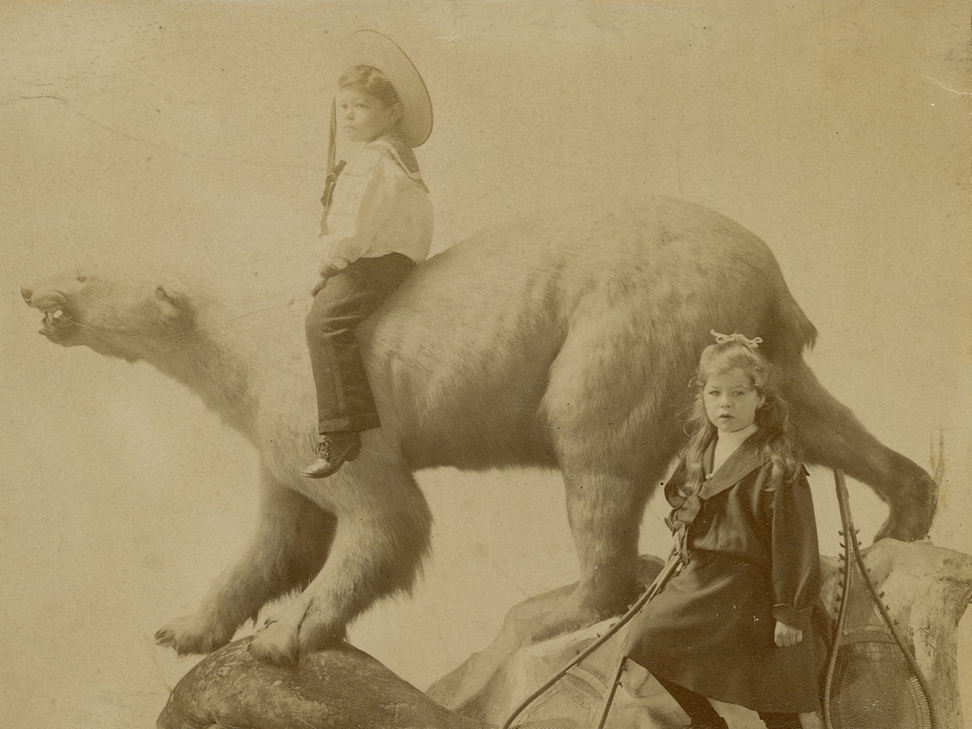 Sepia coloured image of two children on a polar bear