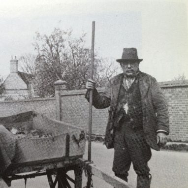 A grainy black and white photograph taken from a newspeper of a man with a staff standing by a cart with a blanket over the edge in a country lane