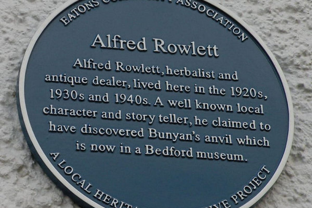 A blue plaque on a white wall about Alfred Rowlett