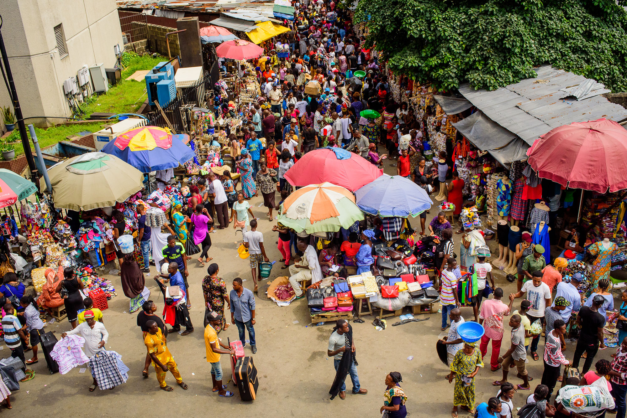 Busy street market with lots of parasols.