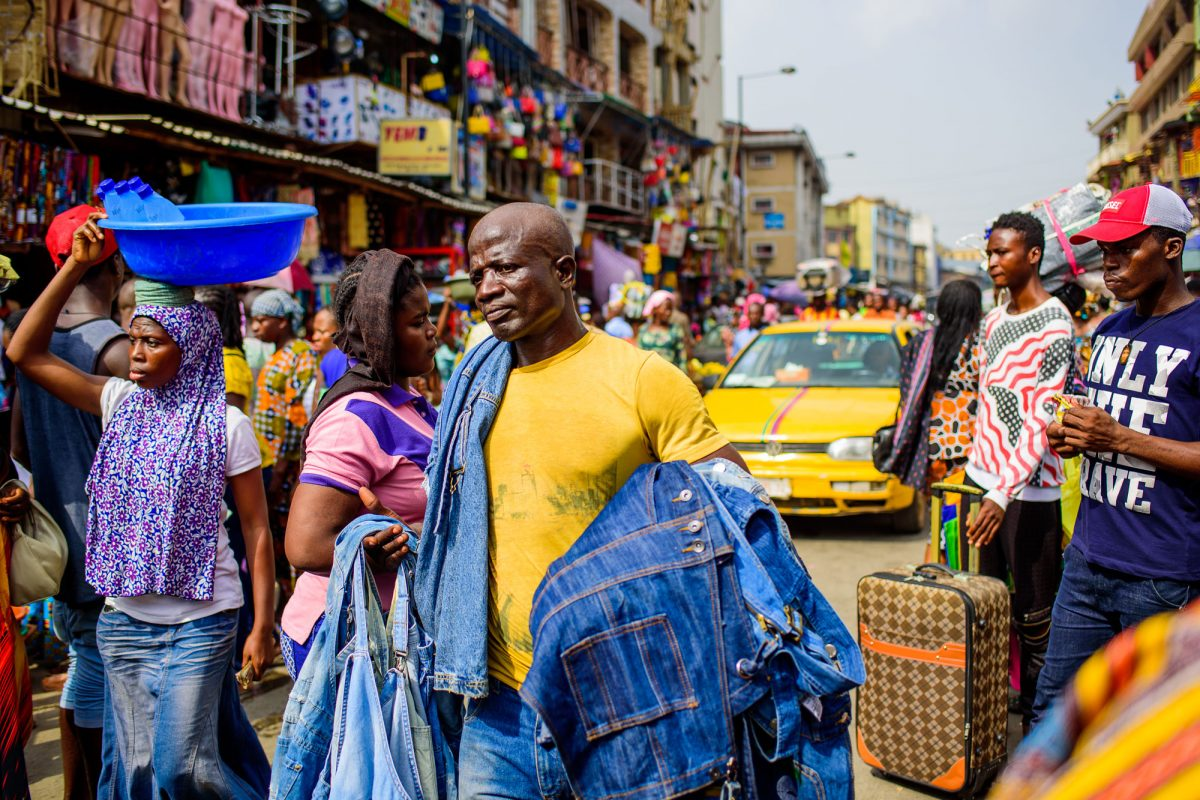 busy market street with man in yellow shirt carrying demin