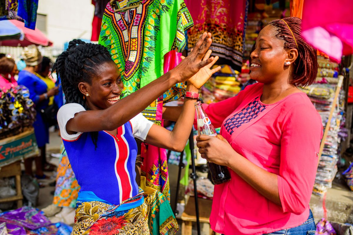 Two women at clothing stall talking.