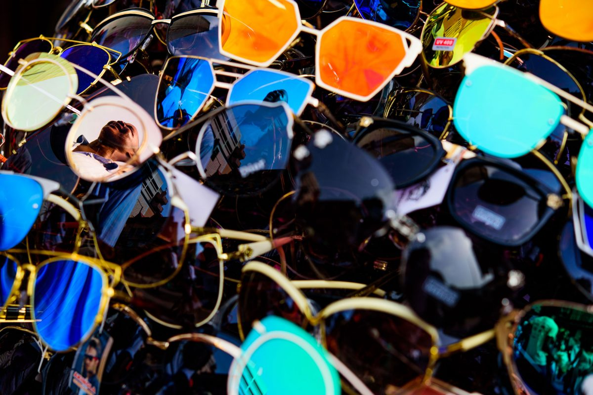 A pile of sunglasses with a woman reflected in some of the lenses.