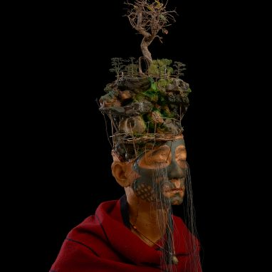Close up of model wearing red clock and tree headdress. Figure has long eyelashes.