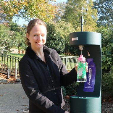A woman is filling a water bottle at a public drinking fountain and is smiling at the camera. She is in a Garden.