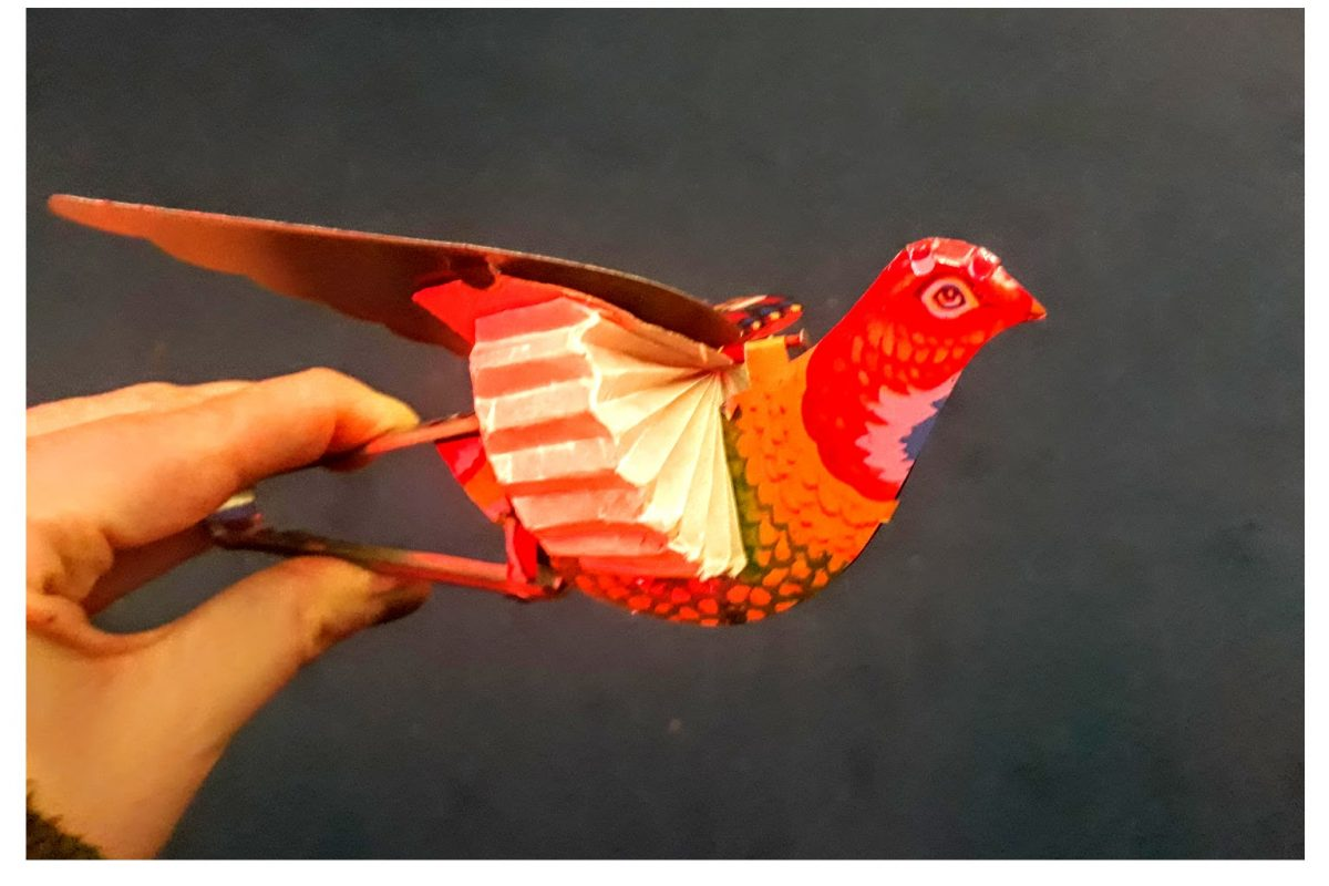 Two images, one on top of the other of a paper red bird with wings which open
