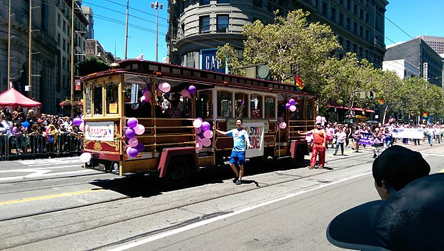 Tram with balloons on it with parade of people walking by in street.