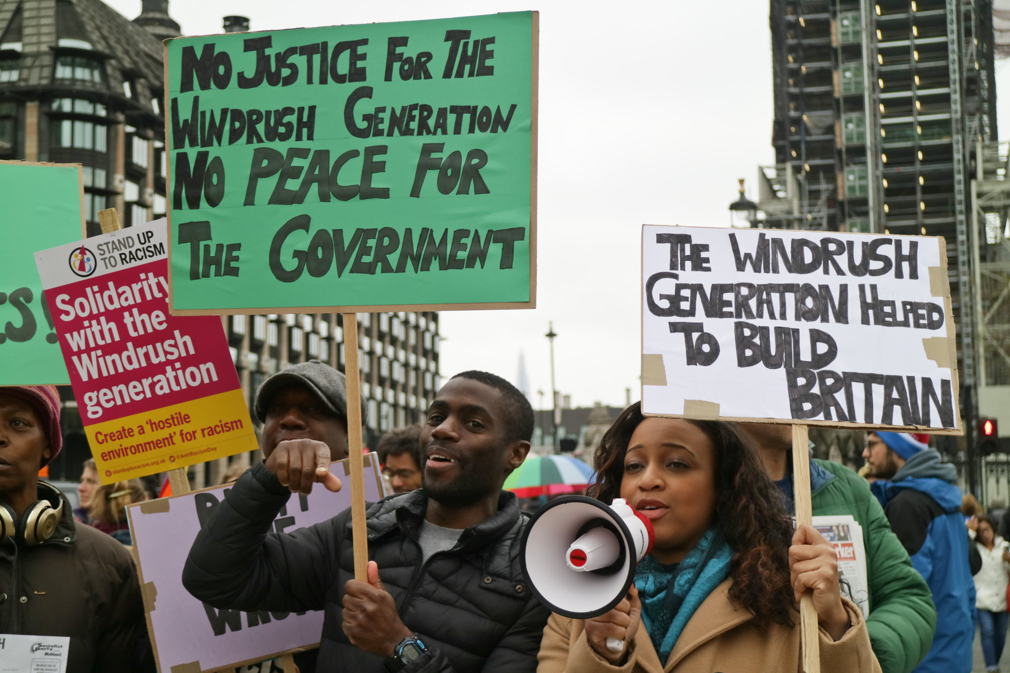 A group of protesters in London. Towards the camera is a woman and a man, both holding placards. The woman is talking into a loudhailer.