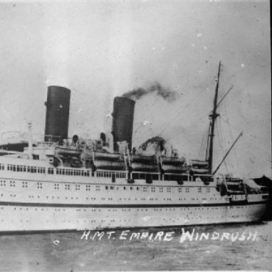 A black and white picture of a large ship with two big chimneys on it