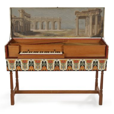 Piano in wooden case with painting of colosseum on the lid.