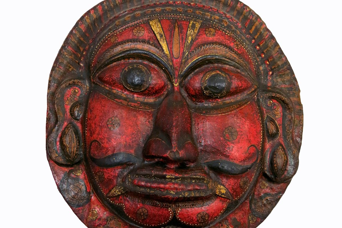 Shield made of painted wood, carved to represent a face, possibly the face of Surya, the god of the sun. The face is painted red, with a black moustache which curls at each side, and there is a caste mark on the forehead.