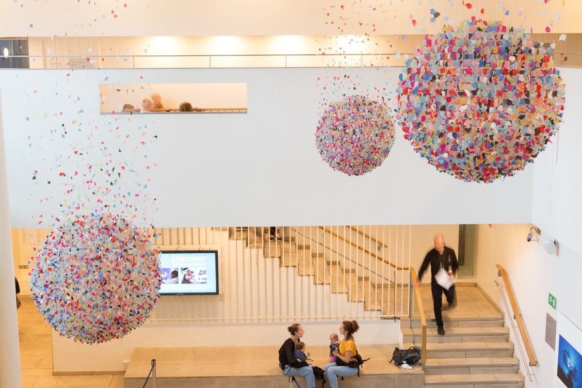 Three spheres suspended from ceiling. People walking around gallery