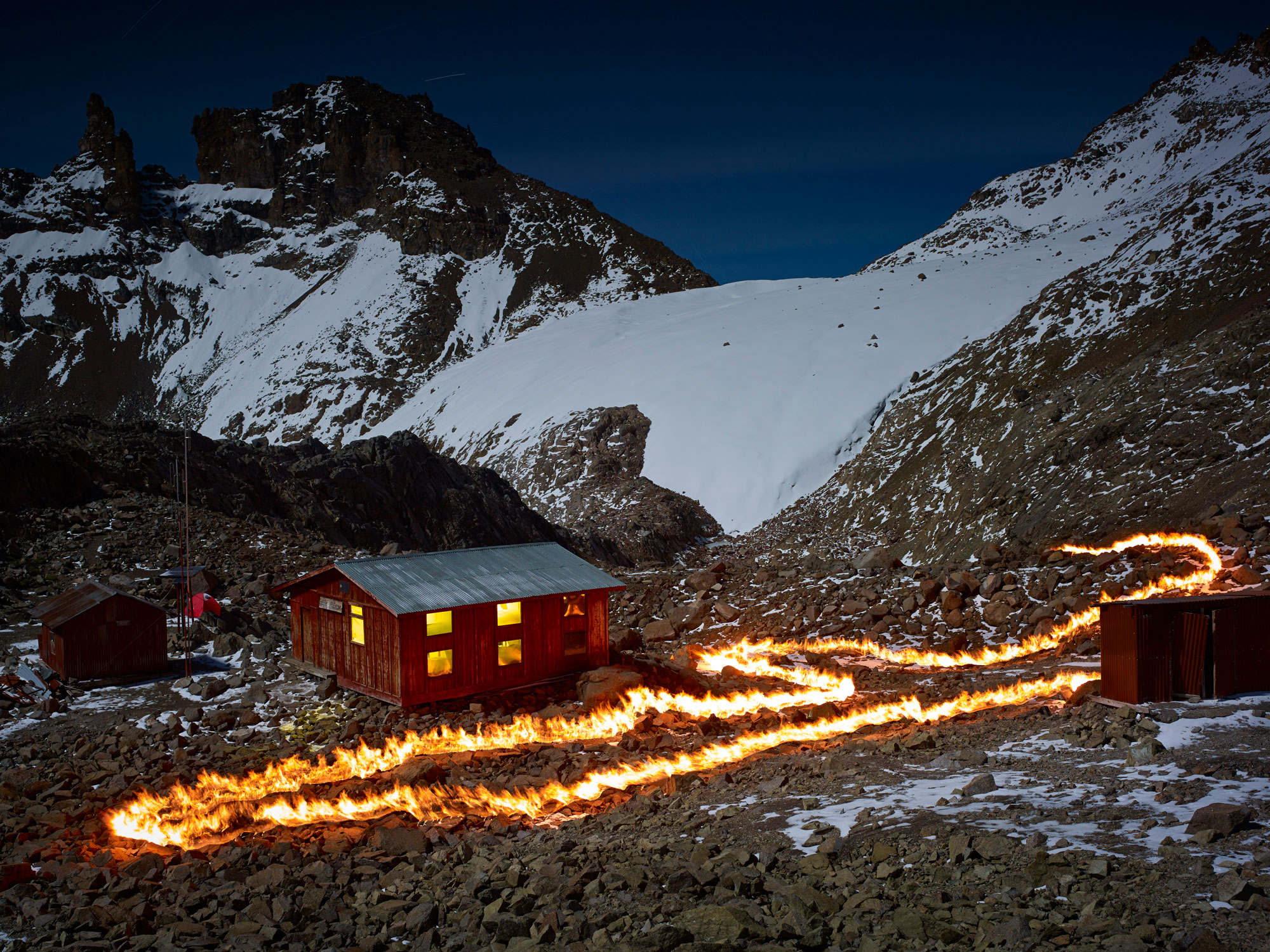 A photograph of a cabin and outbuildings in front of mountain peaks and a snow-covered glacier. A loop of fire runs in front of the cabin.
