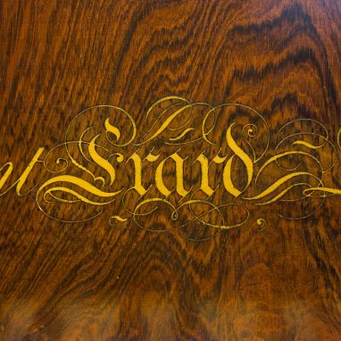 a close up of a piece of varnished wood with cursive script on it saying Erard