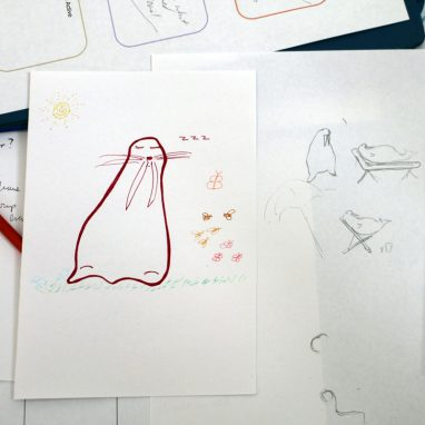 Papers with drawings on them of what look like walruses