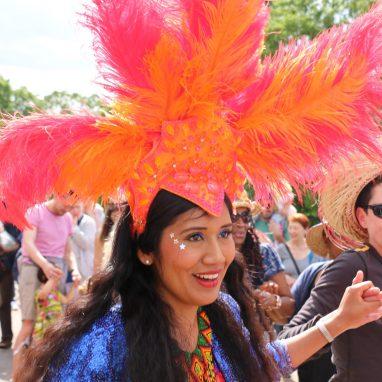 A dancer wearing a headdress is dancing outdoors