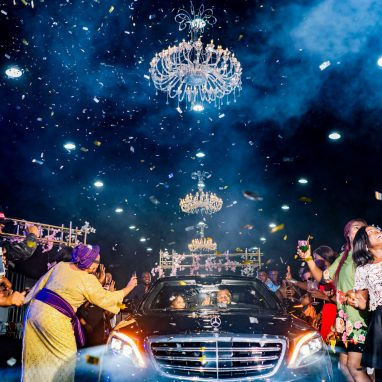 People stand around a car driving off with a couple inside. Everyone is well dressed, taking photos, waving or celebrating. The bacground is black and smoky with hanging lights from the ceiling