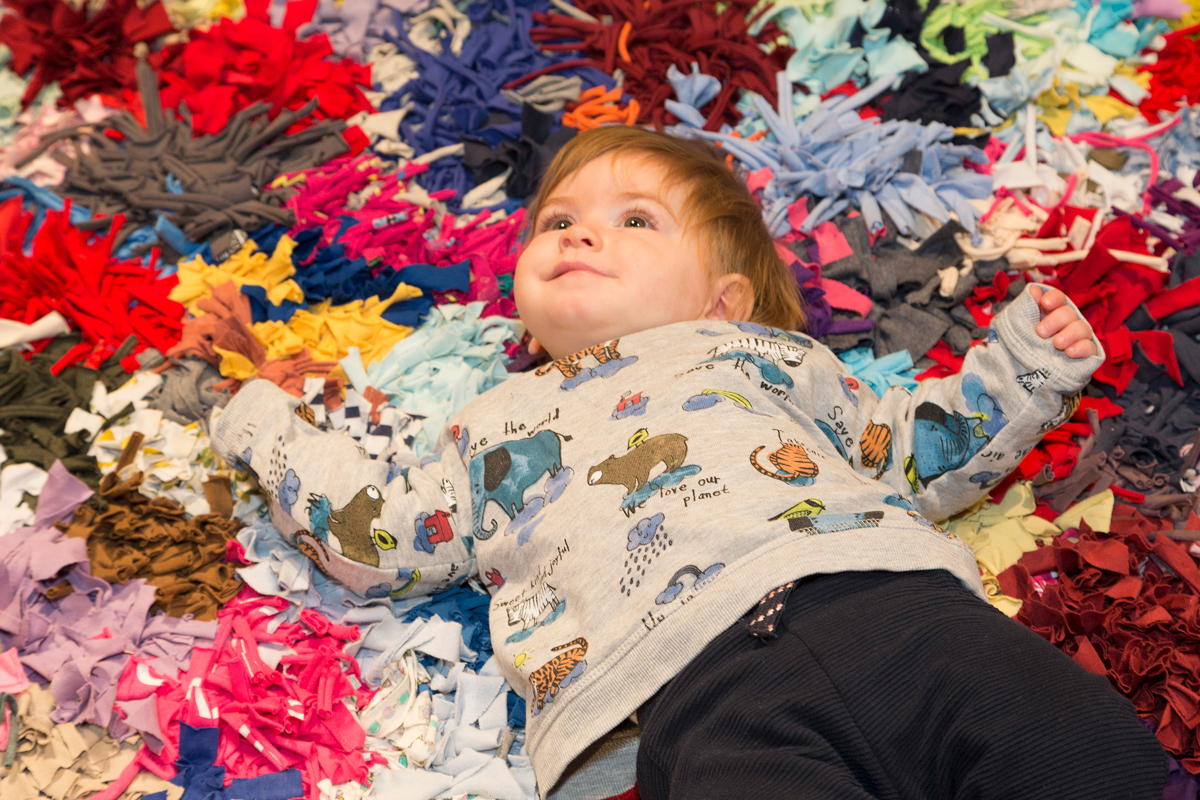 A child on a rag rug