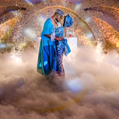 A man and women dressed in blue wedding attire are embracing on a stage surrounded by dry ice around their feet. There are lights in the background