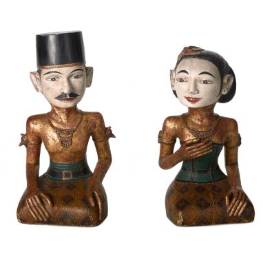 Two figures - a man on the left and woman on the right - decorated in gold leaf. They are both sat down with crossed legs