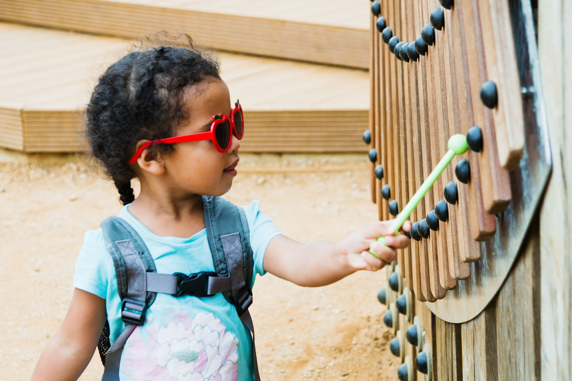 A small girl wearing red sunglasses is side on playing a large outdoor, vertical instrument made of panels of wood with a beater