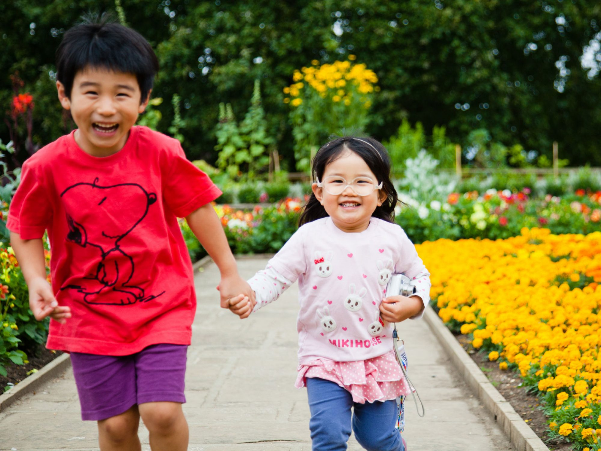 A boy and a girl hold hands laughing as they run towards the camera. They are in a Garden, running along a paved path. To their right and behind them are colourful flowerbeds with yellow and red flowers
