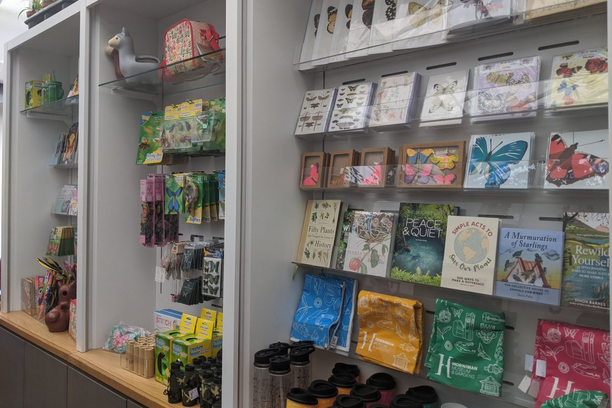 A display of goods in a shop, showing cards, pictures, tea towels, books and toys