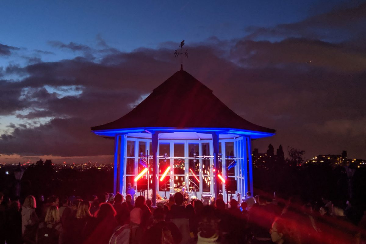 Is is evening and the sky is darkening. There is a small structure with glass windows in front of the camera with red and blue lights shining from it and a performer singing. A crowd is seen looking towards it from behind.
