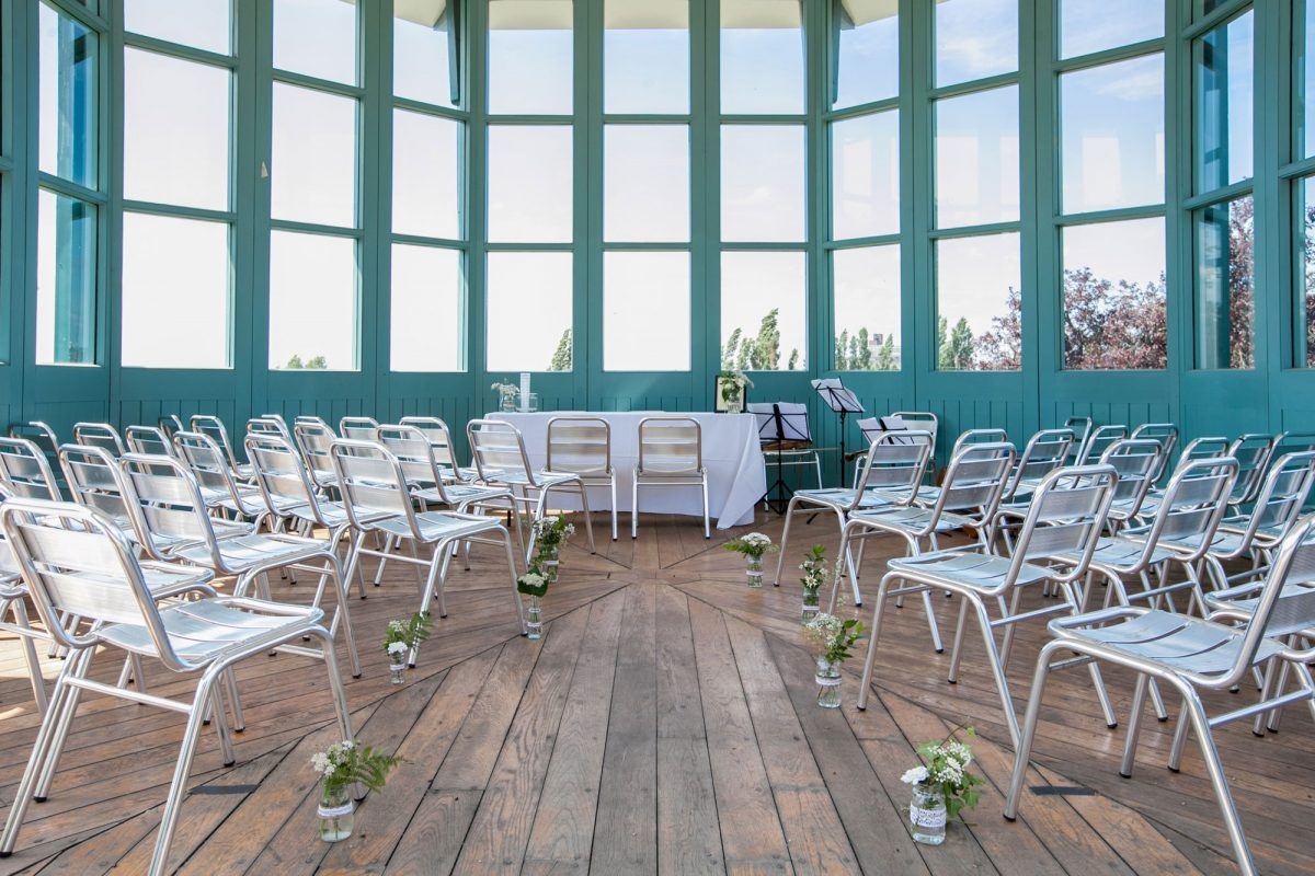 A room surrounded by windows with the surrounds painted blue green. There are chairs facing towards the windows with a table at the end and flowers decorating the wooden floor
