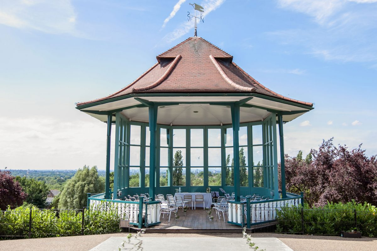 A bandstand, with windows looking out over a view of trees and a city skyline. There are chairs in the bandstand facing the front and jars with flowers in them leading up to the bandstand