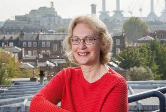 A woman seen from the waist up standing outside with a city skyline in the background. She is wearing a red top, has her arms crossed and is smiling at the camera.